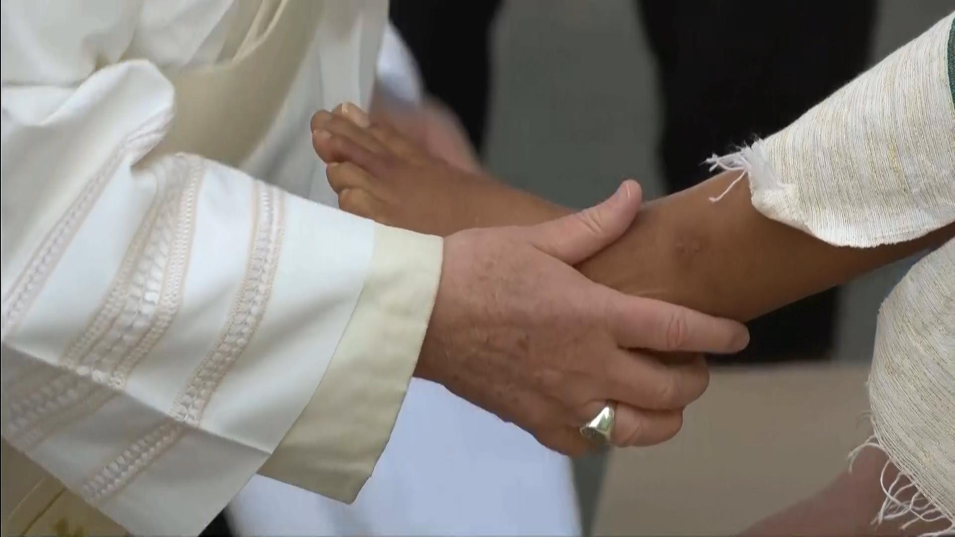 Pope Francis caresses the foot of a refugee staying in Rome, as part of the Mandatum ceremony on Holy Thursday