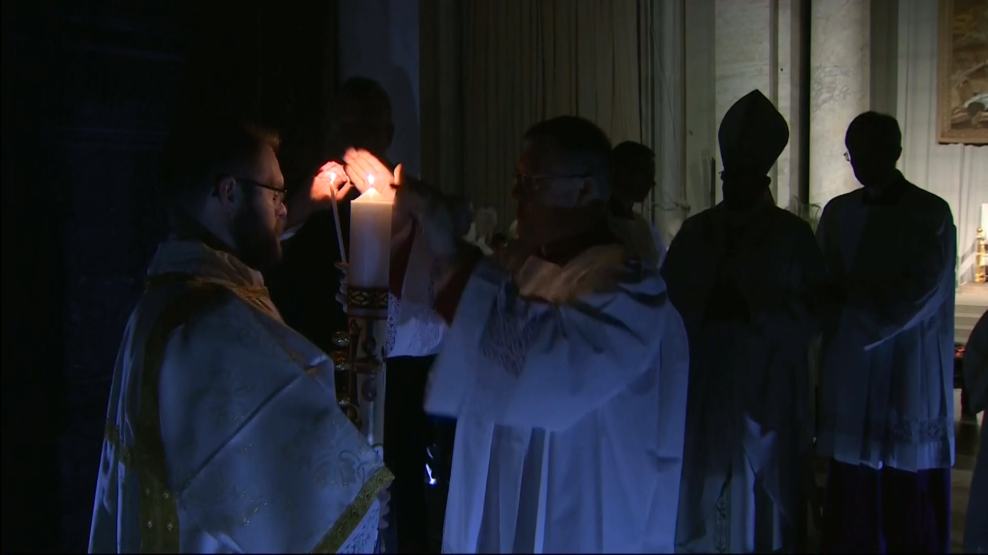 Passing on the light of Christ at Vatican Easter Vigil Mass.