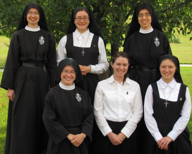 Passionist novitiate photo shows one nun in full vows, two in temporary vows, two postulants and and aspirant. God willing the postulants will become novices, wearing habits with white veils, and the aspirant will take on the postulant's jumper and short veil. Used with Permission