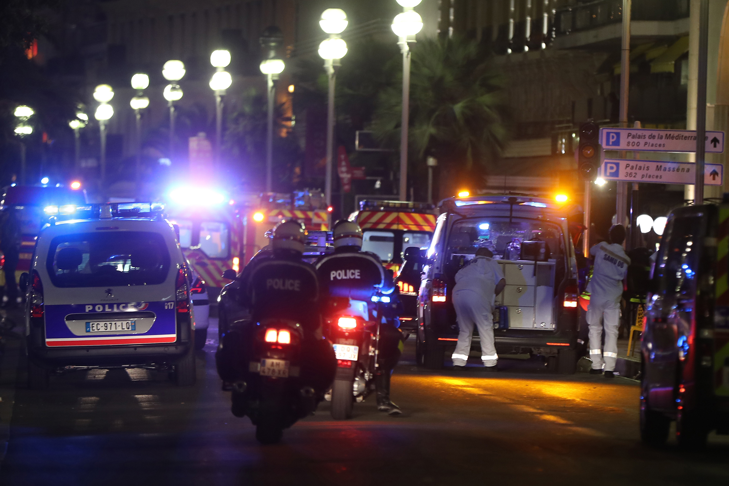 Police officers and rescue workers arrive at the scene of an attack on July 14, 2016, after a van ploughed into a crowd leaving a fireworks display in the French Riviera town of Nice. The mayor of the French city of Nice said dozens of people were likely killed after a van rammed into a crowd marking Bastille Day in the French Riviera resort today and urged residents to stay indoors.  / AFP PHOTO / VALERY HACHE