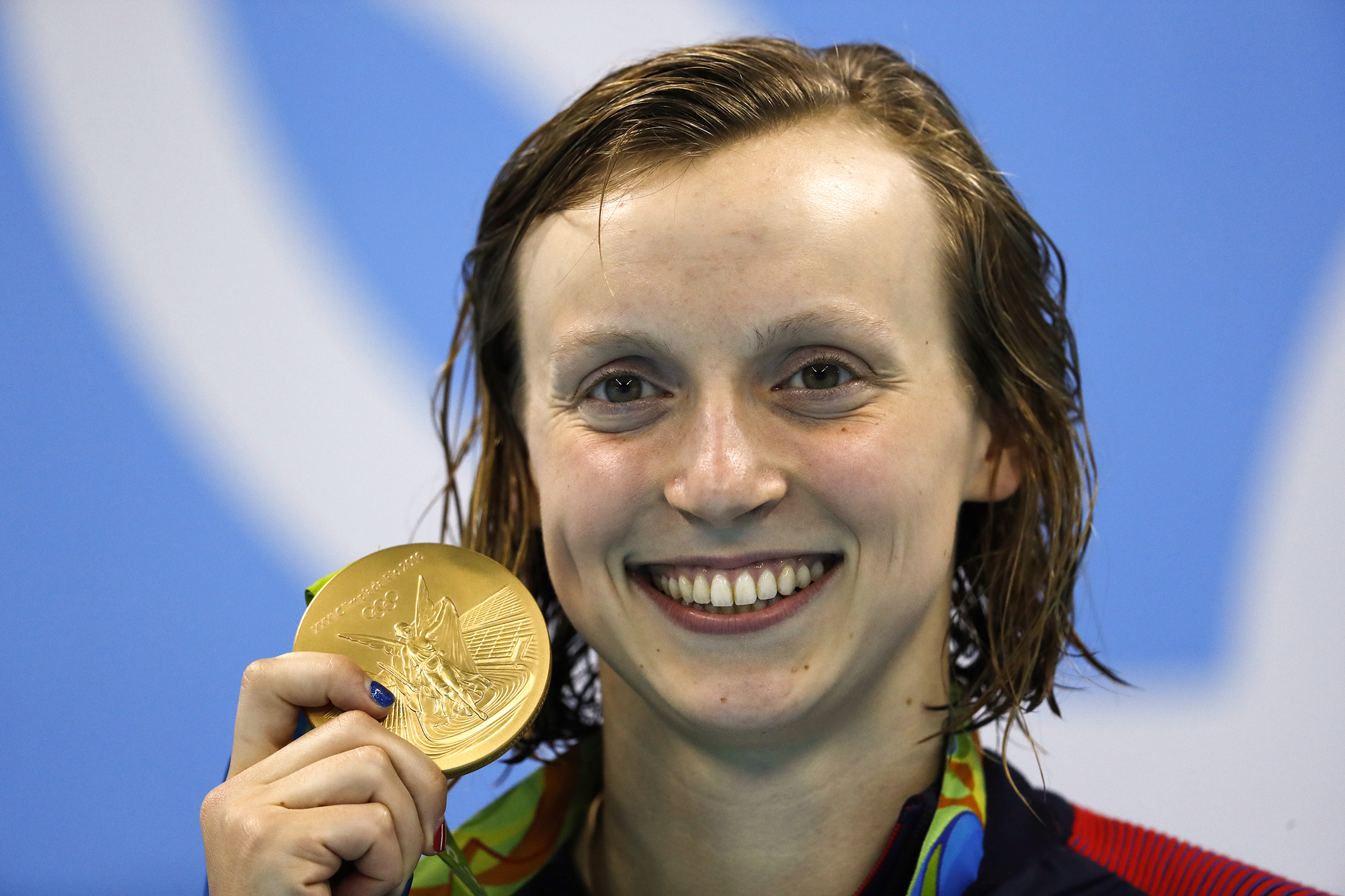 USA's Katie Ledecky poses on the podium with her gold medal after she won the Women's 200m Freestyle Final during the swimming event at the Rio 2016 Olympic Games at the Olympic Aquatics Stadium in Rio de Janeiro on August 9, 2016.   / AFP PHOTO / Odd Andersen