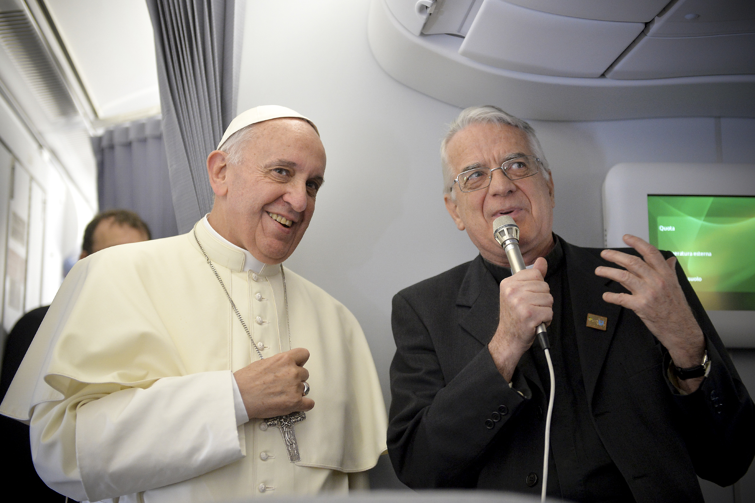 Pope Francis (L) and father Federico Lombardi greet journalists of the papal flight upon arrival in Rio de Janeiro on July 22, 2013. Pope Francis landed in Brazil on Monday for his first overseas trip as pontiff to attend the international festival World Youth Day in Brazil, the world's biggest Catholic country.    AFP PHOTO/LUCA ZENNARO/POOL / AFP PHOTO / POOL / LUCA ZENNARO