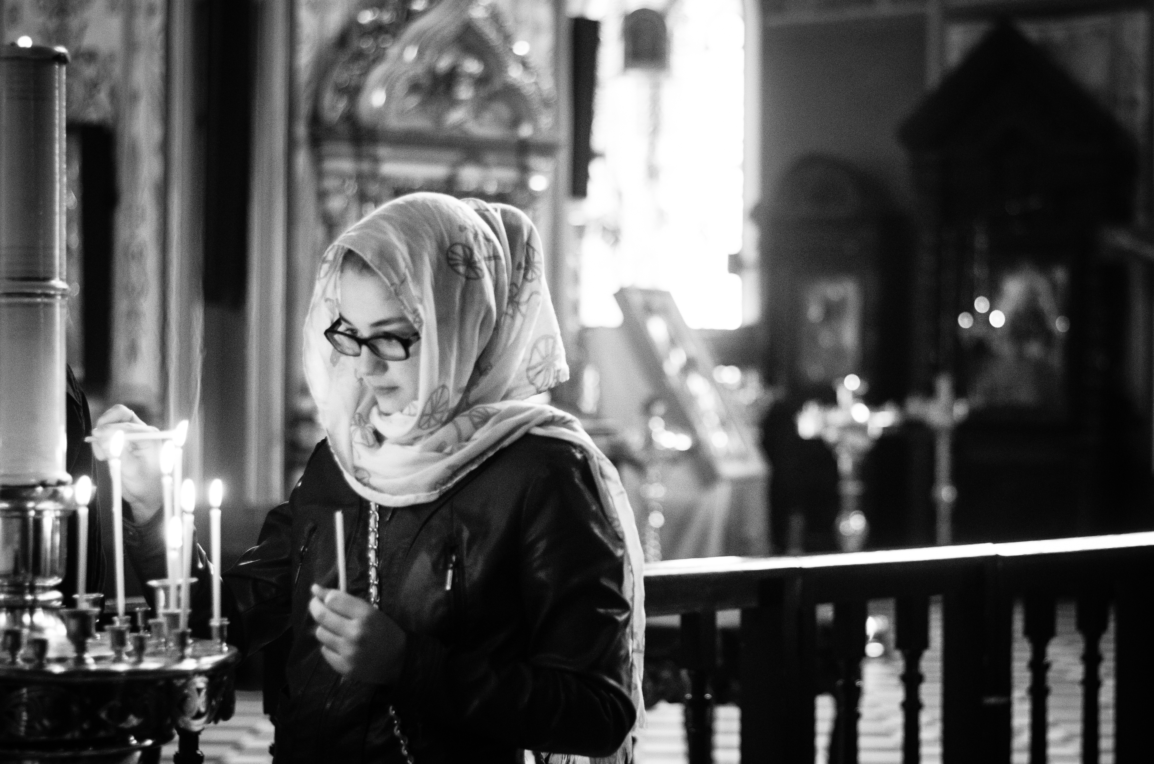 Orthodox woman lights candle in church in Estonia