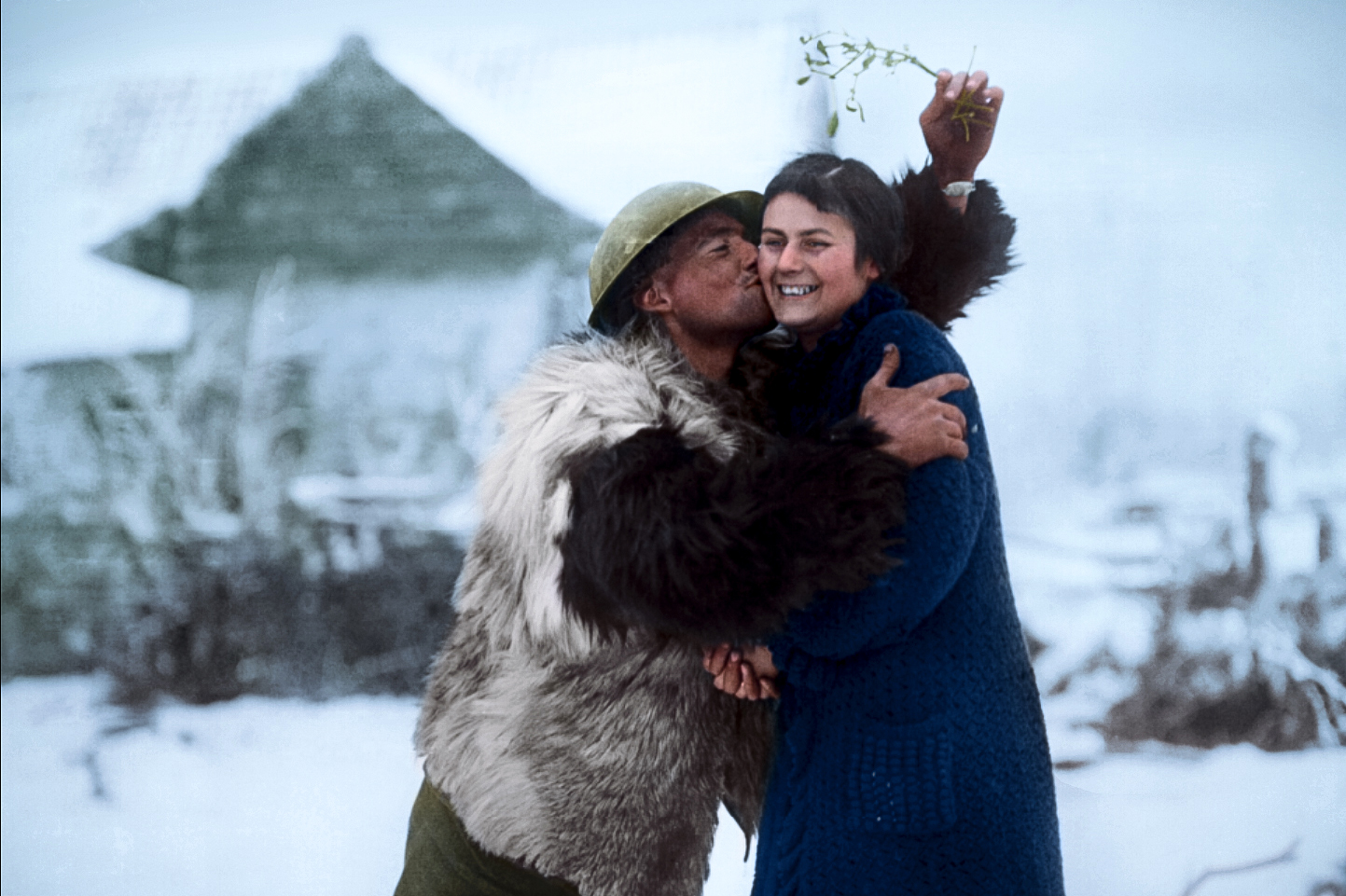 A soldier of the Machine Gun Corps in a sheepskin coat kissing a French farm-girl under a sprig of mistletoe, near Hesdin, 20 December 1917.
