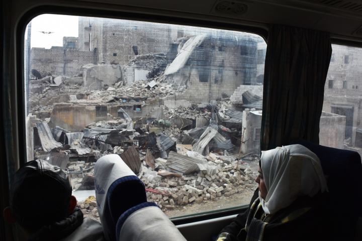 A Syrian woman peers out the window as she sits in a train travelling through Aleppo's devastated eastern districts for the first time in more than four years, on January 25, 2017. It is the train's first such trip since rebels overran east Aleppo in the summer of 2012, effectively dividing the northern city into a regime-held west and a rebel-controlled east. / AFP PHOTO / George OURFALIAN