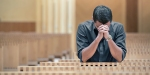 YOUNG MAN PRAYING AT CHURCH