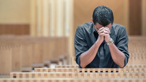 YOUNG MAN PRAYING AT CHURCH