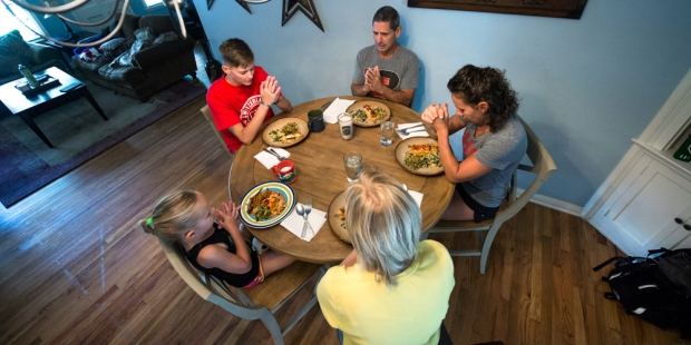 FAMILY PRAYS BEFORE DINNER