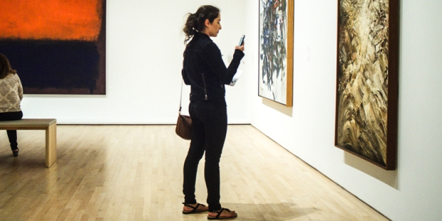 GIRL VIEWING ART ON PHONE,ART GALLERY
