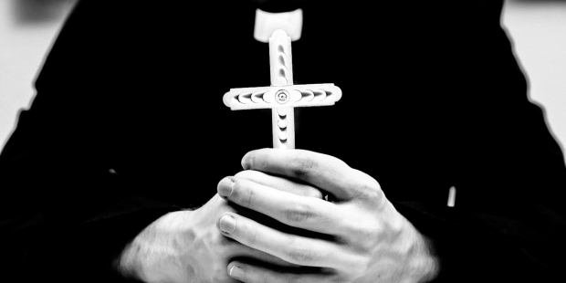 PRIEST HOLDING CROSS