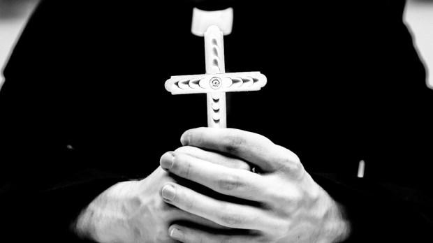 PRIEST HOLDING CROSS