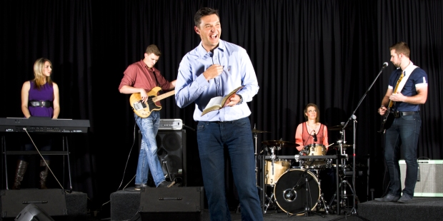 MAN WITH BIBLE PREACHING ON STAGE