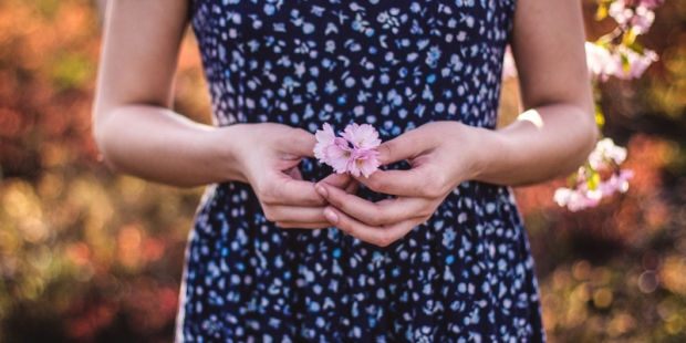 WOMAN HOLDING PINK FLOWER OVER BELLY