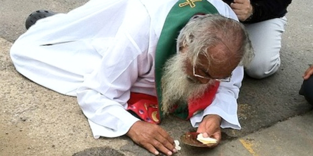 MAN ON GROUND WITH EUCHARIST