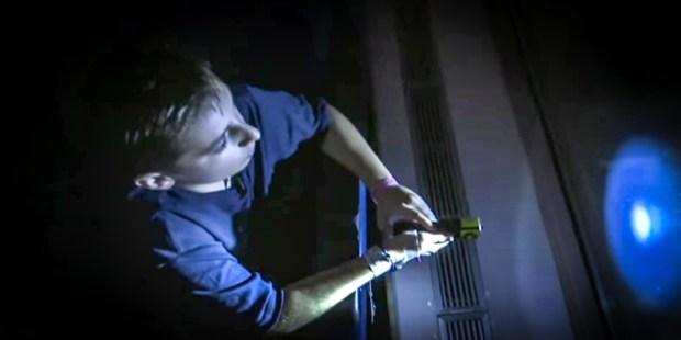 BOY SHINING LIGHT IN WINDOW