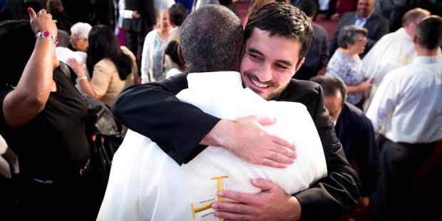MAN HUGGING PRIEST