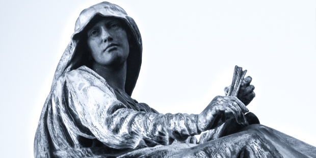 STATUE OF WOMAN HOLDING BIBLE