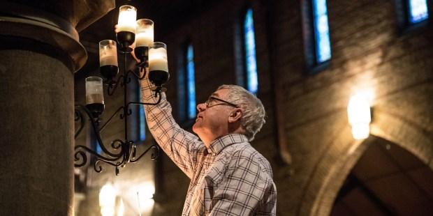 MAN LIGHTING CHURCH CANDLES