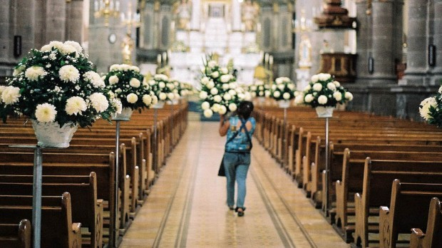 WOMAN DECORATING CHURCH WITH FLOWERS