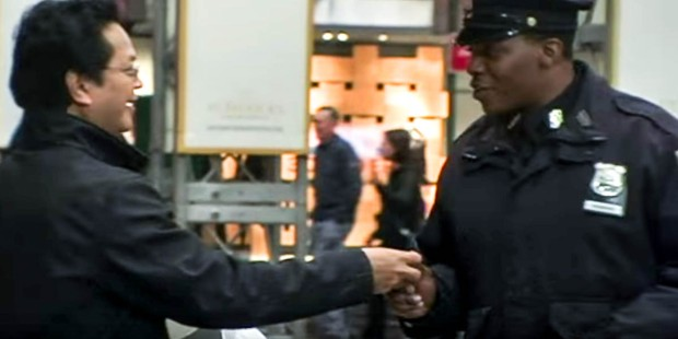 MAN HANDING A POLICE OFFICER A CANDLE