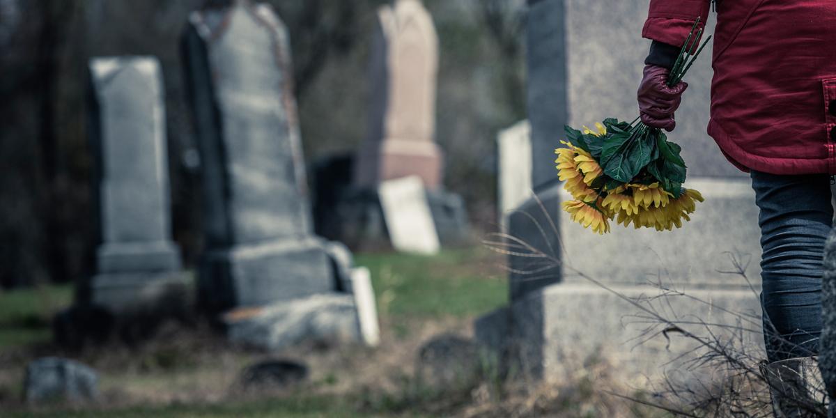 WOMAN,FLOWERS,CEMETERY