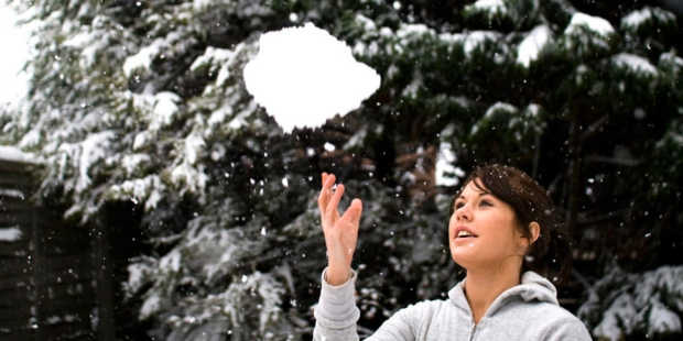 WOMAN TOSSING SNOWBALL