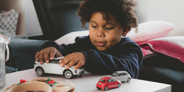 LITTLE BOY PLAYING WITH CARS