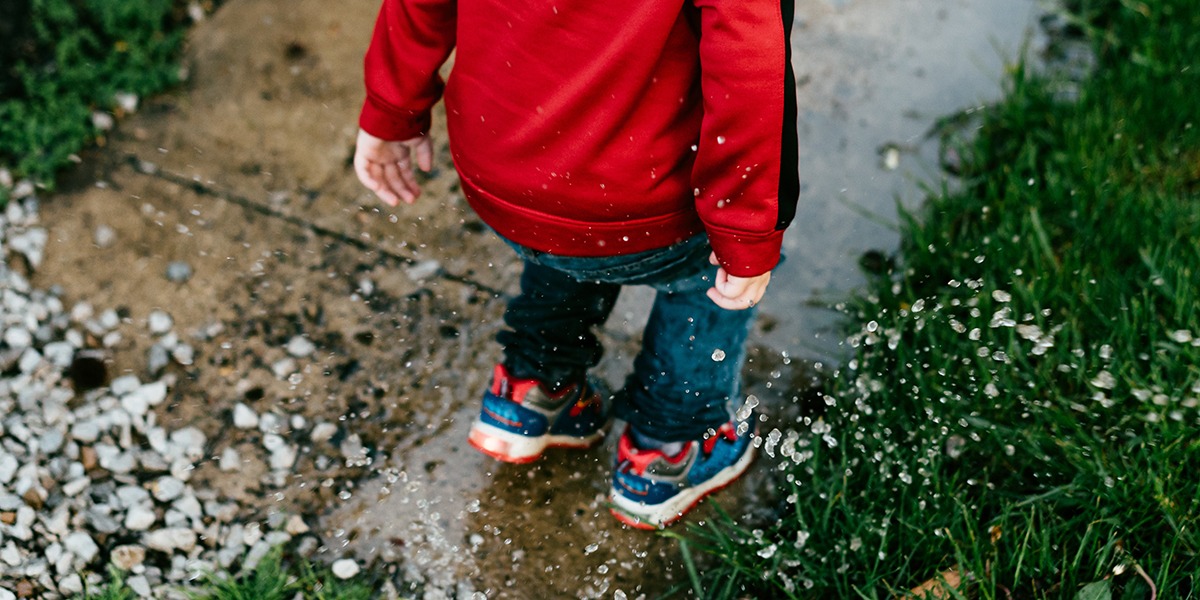CHILD PLAYING IN PUDDLE