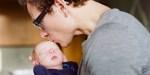 FATHER KISSING NEWBORN