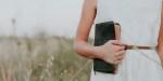WOMAN,HOLDING,BIBLE,FIELD