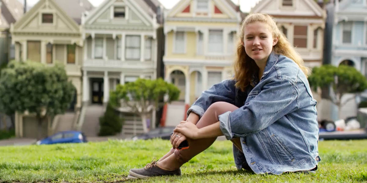 YOUNG GIRL,SITTING ON GRASS