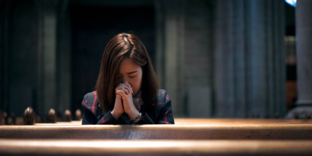 WOMAN PRAYING,CHURCH PEWS